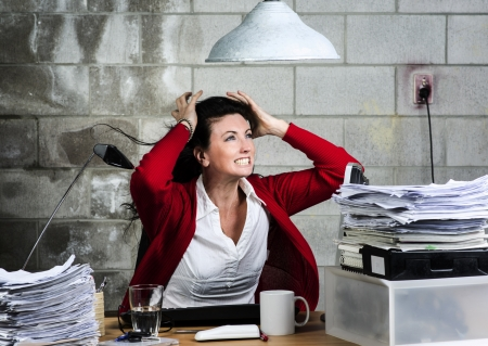 An image of a Caucasian woman with long black hair and a red cardigan in a basement office photo