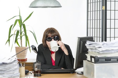 An image of a mature office worker behind her desk