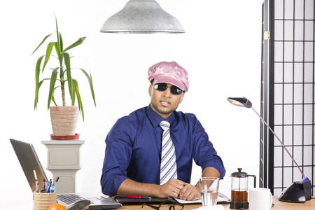 An image of an Indian office worker with a blue shirt behind his desk photo