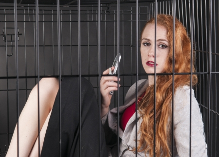An image of a girl with red hair locked up in a cage Stock Photo - 23829013