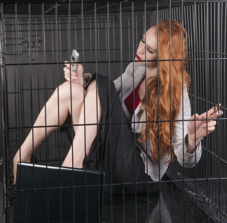 An image of a girl with red hair locked up in a cage photo