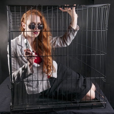 An image of a girl with red hair locked up in a cage Stock Photo - 23829100