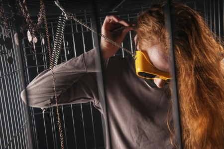 An image of a girl with red hair locked up in a cage Stock Photo - 23829114