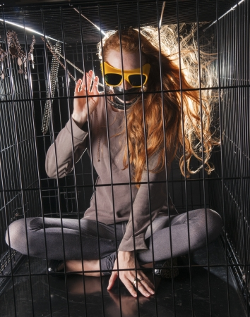 An image of a girl with red hair locked up in a cage Stock Photo - 23829117