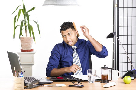 An image of an Indian office worker with a blue shirt behind his desk Stock Photo - 24079003