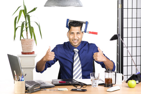 An image of an Indian office worker with a blue shirt behind his desk