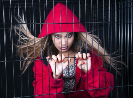 An image of a pretty young Asian girl in a cage against a black background photo