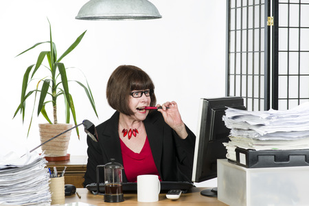 An image of a mature office worker behind her desk photo