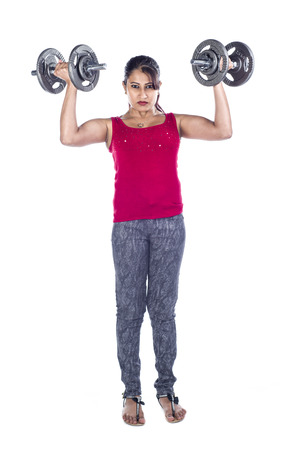 In Indian female in the studio with dumbbells against a white background