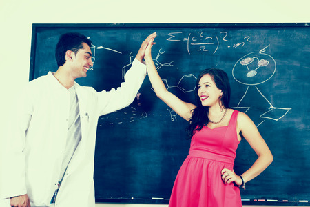 An image of a science teacher with a student in a class room Stock Photo
