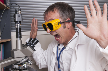 An image of a male researcher working with a microscope Stock Photo