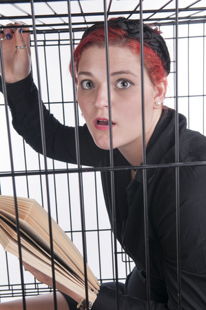 A young woman with red hair locked up in a cage Stock Photo - 26121440
