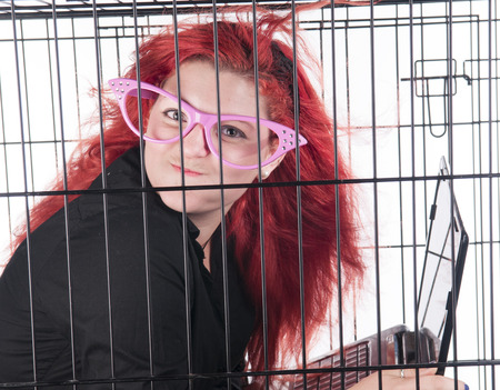 A young woman with red hair locked up in a cage photo