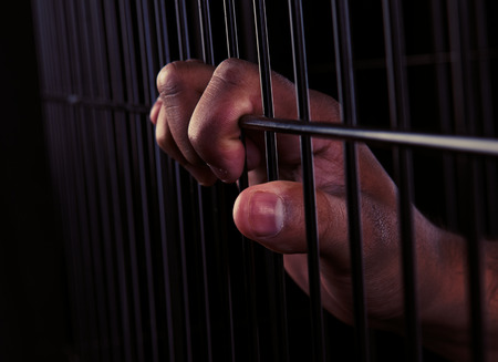 A hand of a man trapped in a cage photo