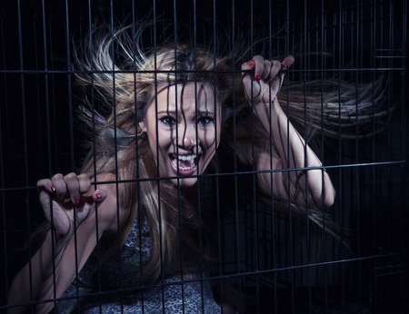 A young blonde asian girl in a cage photo