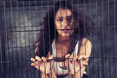 A scared Indian girl locked up in a cage photo
