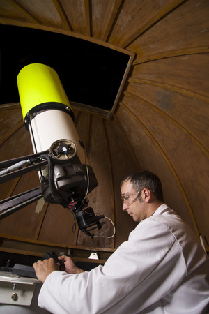 A Caucasian scientist working with a a large telescope Stock Photo