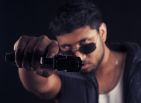 An Indian young man in a studio against a black  photo