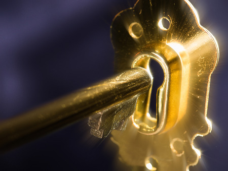 A golden key in a keyhole illuminated by a mysterious radiant light from the other side isolated on black background.