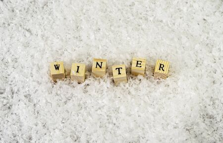 the word winter made of letters on wooden cubes on a snow background  3