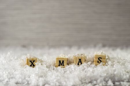 x mas word made of letters on wooden cubes on a snow background 4 Banque d'images - 138371826