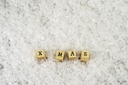 x mas word made of letters on wooden cubes on a snow background Banque d'images - 138371740