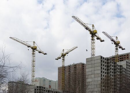 Houses under construction and construction cranes