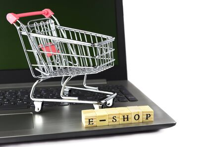 e - shop folded with cubes with letters on the background of a laptop and trolley