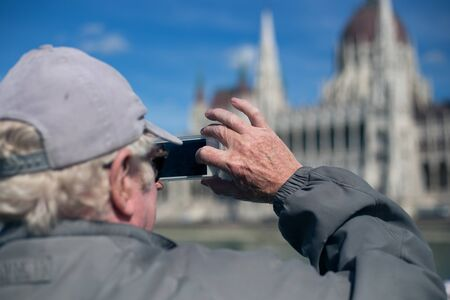 Old elderly pensioner tourist makes a photo of the sights of the parliament building in Budapest