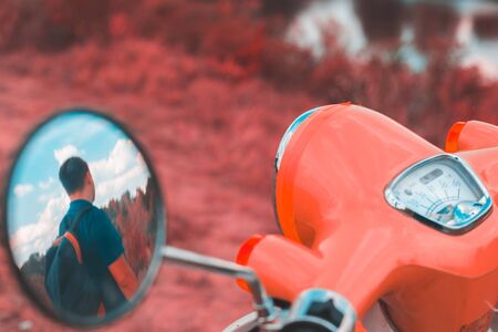 Reflection of a man in the side mirror of a motorbike