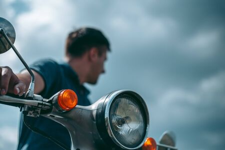 Man with motorbike looking to the side