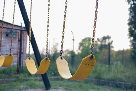 Yellow rubber swing on chains in the backyard Stockfoto