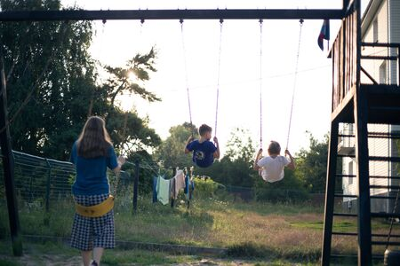 Kids in the backyard swing at sunset Фото со стока