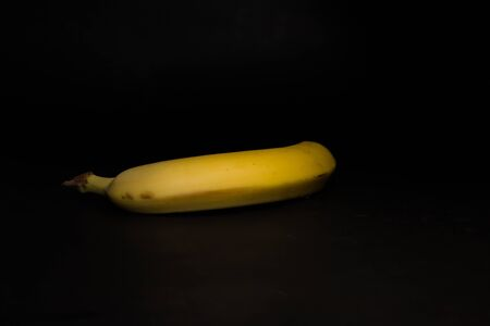 Yellow ripe banana on a black background