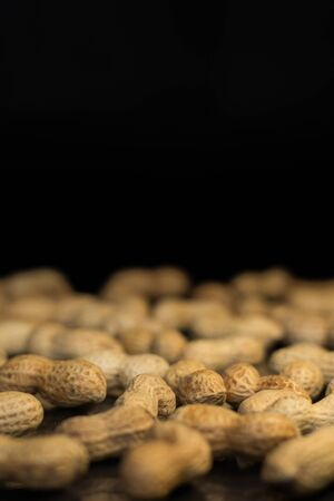 Ripe unroasted peanuts in husk and background