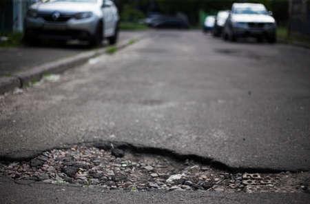 Broken asphalt and cracks on the road surface