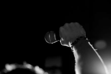Young handsome guy emotionally sings and speaks into the microphone. Black and white photography Reklamní fotografie