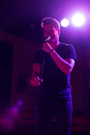 Young handsome guy emotionally sings and speaks into the microphone Reklamní fotografie