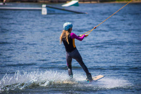The man does wakeboarding on the water in the summer in a helmet and wetsuit.