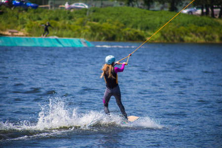 The man does wakeboarding on the water in the summer in a helmet and wetsuit. Stock Photo