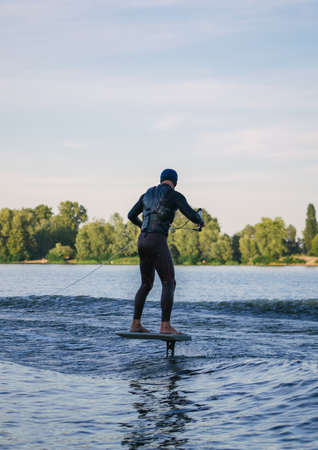 Man on a wakeboard in the river at daytime