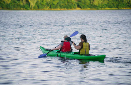 Couple paddling a kayak in the river at daytime