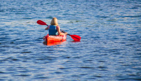 Woman paddling a red kayak in the river at daytime Stock Photo