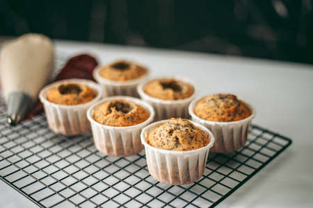 Delicious appetizing fresh baked muffins in the kitchen close up