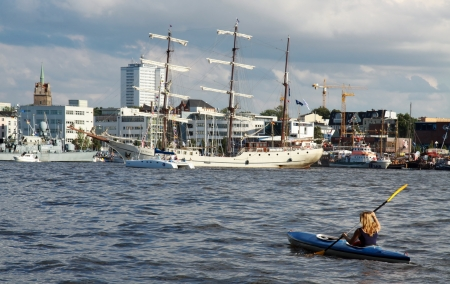 yachtsman: PORT ROSTOCK, GERMANY - AUGUST 8: Young women join the sailing ship parade with  her kayak on August 8, 2012 during the 22nd annual Hanse-Sail event in Port Rostock, Germany