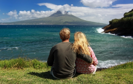 Young couple observe Volcano Mount Pico from the coast of Faial, Azores Standard-Bild