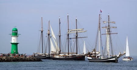 PORT WARNEM�NDE, GERMANY - AUGUST 10  Old dutch Sailing ships  Banjaard ,  Ide Min  and  Hendrika Bartelds  passing the light beacon on August 10, 2013 in the scope of the 23  Hanse-Sail  at the port Rostock-Warnem�nde  Mecklenburg-Vorpommern, Germany