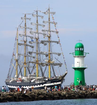 yachtsman: PORT WARNEMÜNDE, GERMANY - AUGUST 10  Old russian Sailing ship  Kruzenstern  is passing the light beacon on August 10, 2013 in the scope of the 23   Hanse-Sail  at the port Rostock-Warnemünde  Mecklenburg-Vorpommern, Germany