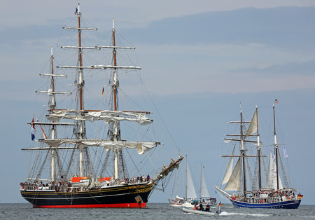 PORT WARNEMUENDE, GERMANY - AUGUST 09  Old dutch and german Sailing ships Stad Amsterdam and Santa Barbara Anna passing the light beacon on August 09, 2014 in the scope of the 24  Hanse-Sail at the port Rostock-Warnemuende, Germany