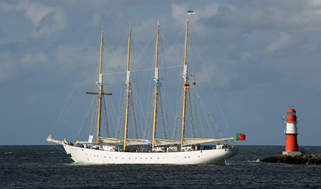 PORT WARNEMUENDE, GERMANY - AUGUST 09 Old portuguese sailing ship Santa Maria Manuela is passing the light beacon on August 09, 2014 in the scope of the 24th Hanse-Sail at the port Rostock-Warnemuende - Mecklenburg-Vorpommern, Germany
